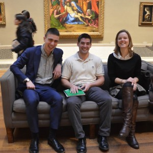 Student Curators Lucas, Charles and Kate seated before Solario's Lamentation